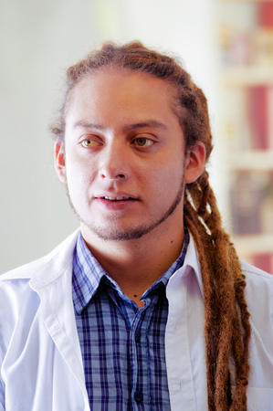 Young doctor with long dread locks posing for camera, clinic in background, medical concept