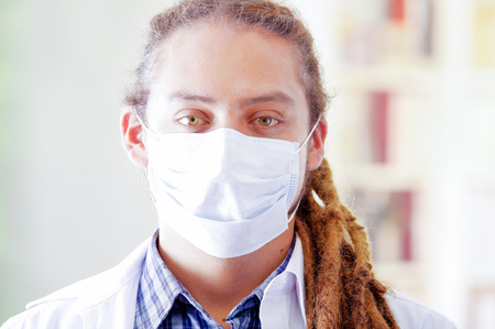 Young doctor with long dread locks posing for camera, wearing facial mask covering mouth, clinic in background, medical concept Stock Photo