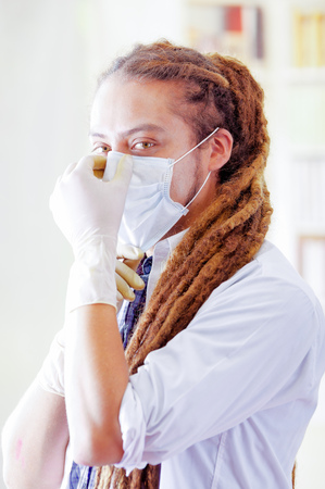 Young doctor with long dread locks posing for camera, adjusting facial mask covering mouth, clinic in background, medical concept