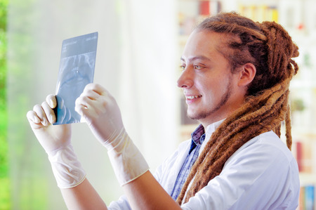 Young doctor with long dread locks posing for camera, holding up x ray image staring at it, clinic in background, medical concept Stock Photo