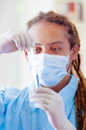 Young doctor with long dread locks posing for camera preparing syringe, wearing facial mask covering mouth, clinic in background, medical concept Stock Photo