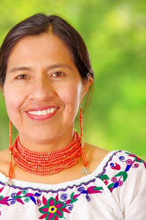 Closeup beautiful hispanic woman wearing traditional andean white blouse with colorful decoration around neck, matching red necklace and ear, posing happily for camera, garden background