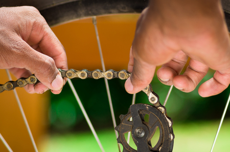 Closeup hand working on mechanical parts next to wheel spokes Stock Photo