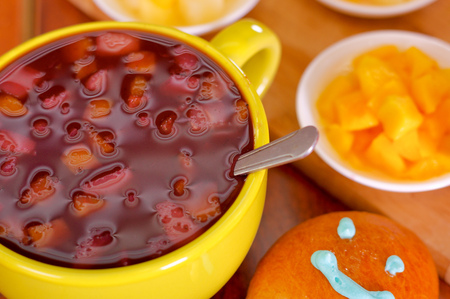 Yellow bowl with traditional tasty latin american colada morada berry juice, symbolizing blood from those deceased, day of the dead concept