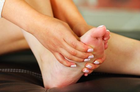 callus: Pain in the foot, auto massage of female feet. Stock Photo