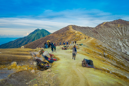 KAWEH IJEN, INDONESIA - 3 MARCH, 2017: Local miners carrying loads of yellow sulfur rocks up mountain side, tourist hiking attraction located inside volcanic crater, spectacular nature