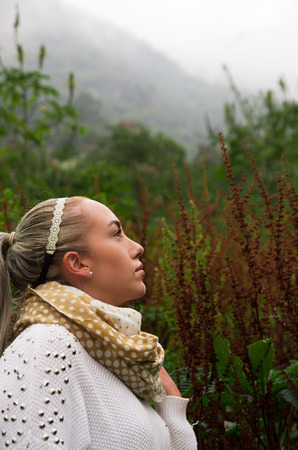 Pretty young reflective woman looking up in a mountain Stock Photo