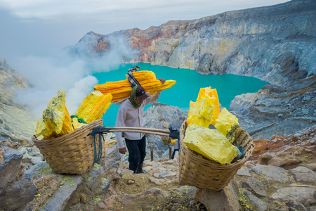 KAWEH IJEN, INDONESIA - 3 MARCH, 2017: Local miners carrying heavy baskets of yellow sulfur rocks up mountain side, tourist hiking attraction located inside volcanic crater, spectacular nature
