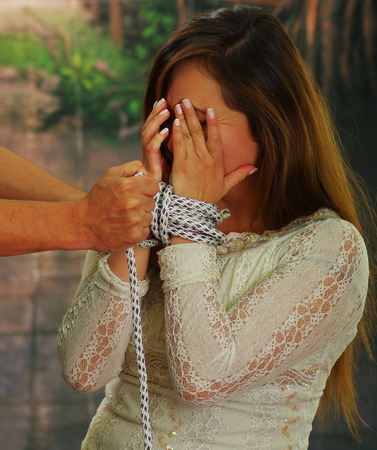 Fearful young woman being tied up by male captor Stock Photo
