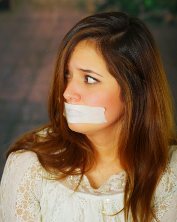Beautiful young hispanic woman tied and mouth taped