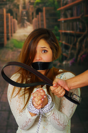 Fearful young woman tied while captor holds belt Imagens