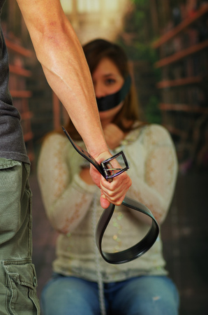 silenced: Man holding belt towards tied up young woman in the background Stock Photo