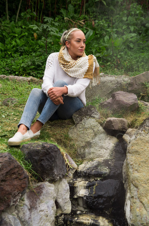 Pretty young pensive girl sitting by some rocks Stock Photo
