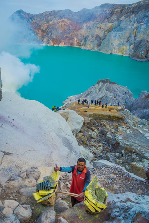 the miners: KAWEH IJEN, INDONESIA - 3 MARCH, 2017: Local miners carrying heavy baskets of yellow sulfur rocks up mountain side, tourist hiking attraction located inside volcanic crater, spectacular nature