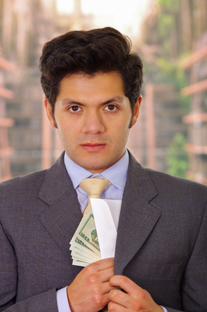 Businessman in dark suit and with tie putting money in his suit Stock Photo