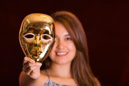 Happy beautiful woman holding a gold mask