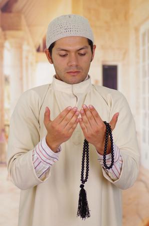 thobe: Cute arabian guy holding a masbaha with his hands Stock Photo