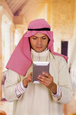 Cute young arabian man using his Tablet Stock Photo