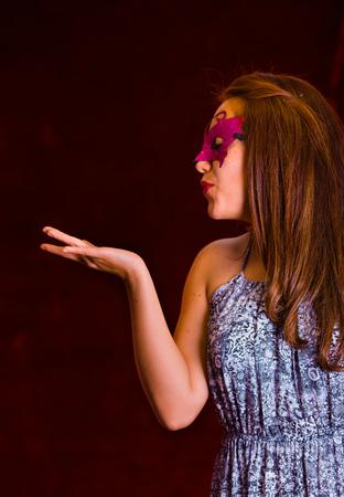Happy beauty woman wearing pink carnival mask sending a kiss