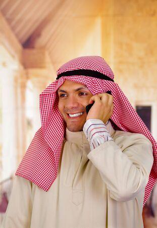 thobe: smiling cute arabian man using his cellphone Stock Photo