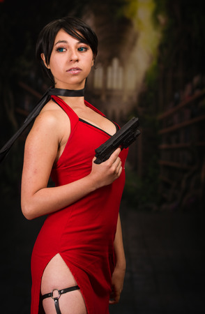 Sexy powerful woman with a red dress holding a gun