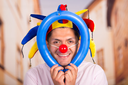 unprofessional: Cheerful young businessman with a red clown nose and colorful harlequin hut in his head playing with a blue ballons around his head