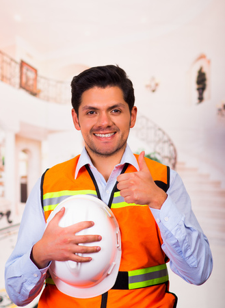 Smiling engineer with a helmet in his hand at construction site Stock Photo