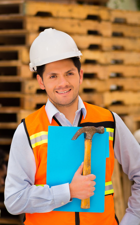 Smiling young engineer holding a folder and hammer in his hand at construction site Stock Photo