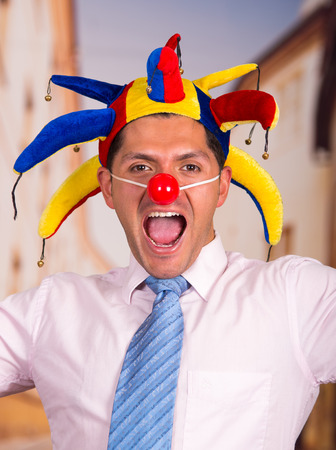 Happy handsome young businessman with a red clown nose and colorful harlequin hut in his head