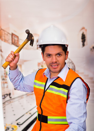 Handsome young engineer holding a hammer in his hand at construction site Stock Photo