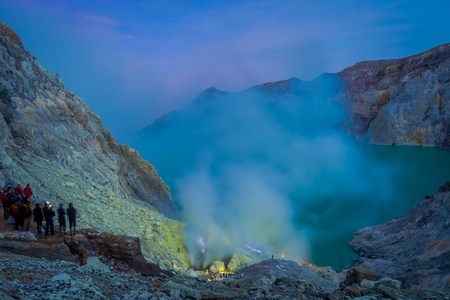 the miners: KAWEH IJEN, INDONESIA: Nice overview of sulfur mine with miners working next to volcanic crater lake, spectacular nature Stock Photo