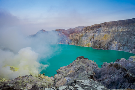 KAWEH IJEN, INDONESIA: Tourist hikers with backpacks and facial masks seen overlooking sulfur mine and volcanic crater Imagens