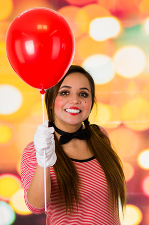 Closeup portrait of cute young girl clown mime holding red balloon