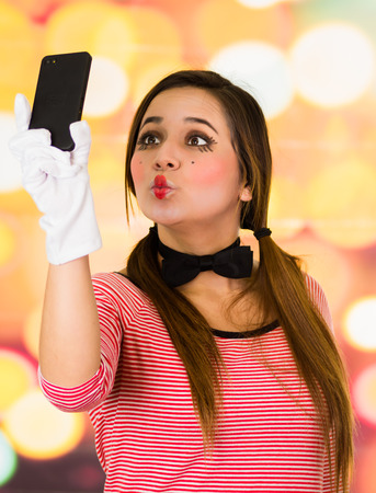 Closeup portrait of cute young girl clown mime taking selfie with cell phone Stock Photo