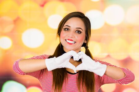 Closeup portrait of female clown mime making a heart with hands