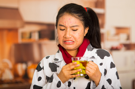 Portrait of young girl with skin problem drinking some tea making silly faces
