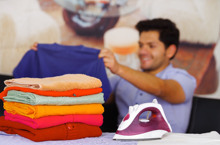 A pile of clothes next to the iron with gorgeous man smiling behind while he is holding a blue sweater