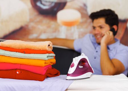 celphone: A pile of clothes next to the iron with gorgeous man smiling behind while he is using a celphone