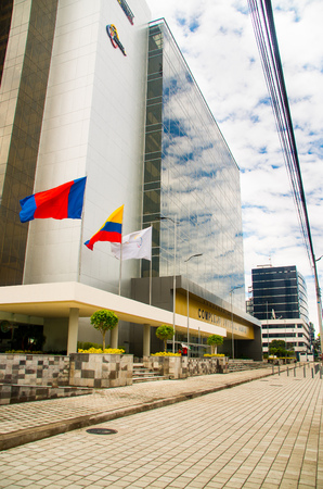 presidency: QUITO, ECUADOR- APRIL 26, 2017: New beautiful building of North judicial complex located in the center of the magnificent city of Quito, built by Rafael Correa presidency with the ecuadorian flag and quito flag Editorial