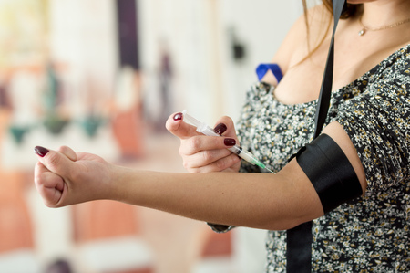 Woman with syringe make an injection to her arm using a black elastic band Stock Photo