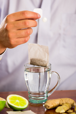 Man preparing a deleighful cup of tea with ginger and lemon home antimicrobial therapy