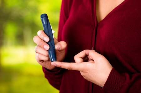 glycemic: Woman with red sweater checking blood sugar level by glucometer and test stripe at home