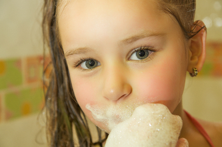 little beautiful girl playing with water and foam with her mouth in bath Stock Photo