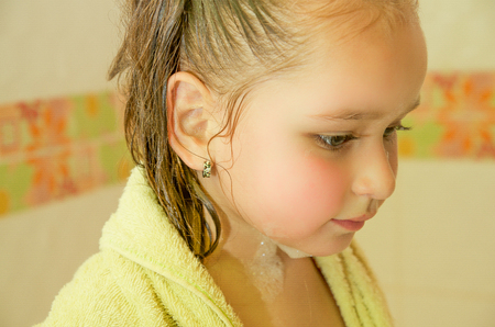 little beautiful girl playing taking a shower in bath with a yellow Bathrobe