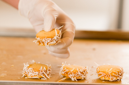 Man moving a cookie with caramelized milk dulce de leche and coconut, Argentine Cookies Alfajores