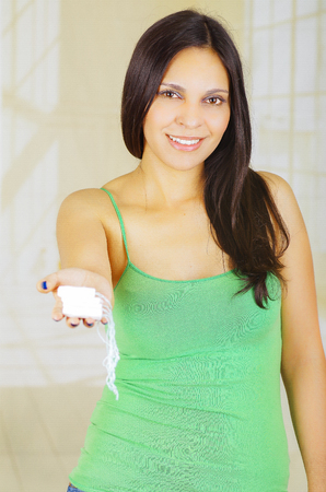 hygenic: Young beautiful woman with a green blouse holding a hygenic towel with one hand and pointing in front of herself Stock Photo