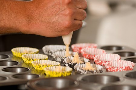 A bakery man is preparing a delicious christmas cookies in a bakery store, adding Dough inside of the cupcake Wrappers Stock Photo