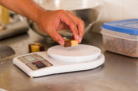 A man is using a food scale digital to weigh a cookie on metallic background Stock Photo