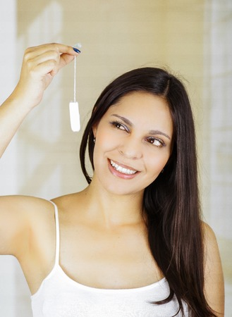 Young beautiful smiling woman holding a menstruation cotton tampon Stock Photo