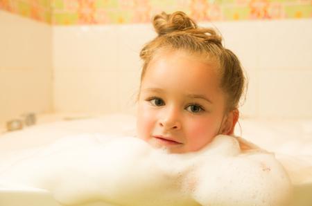 little beautiful girl posing inside of a bathtub with water and foam in bath